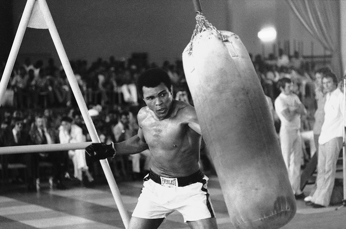 Muhammad Ali working out before his upcoming bout against George Foreman. He is training with heavy bag and jump rope in October 1974. (AP Photo/Horst Faas)
