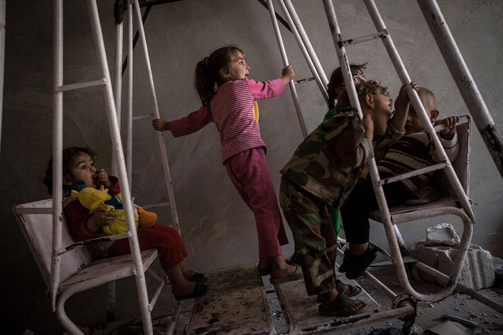 Jueves, oct. 3, 2013. Los nietos de Mohammed Ahmed Kale (no fotografiado) juegan en un columpio dentro de la casa de su familia en Kafr Lata (situada en la cima de una montaña), villa sometida a intensos bombardeos y fuego de mortero debido a los combates entre opositores al gobierno de Bashar Al-Assad y fuerzas del ejército Sirio en la provincia norte de Idlib, Siria. La familia de Mohammed —incluyendo cuatro hijas, y seis hijos con sus respectivas familias— es una de las dos únicas familias que permanecen en la villa. Se han rehusado abandonar su hogar a pesar de los intensos bombardeos y combates, debido a que cuatro de sus hijos forman parte de los milicianos luchando en el frente de batalla situado a un kilómetro de distancia.